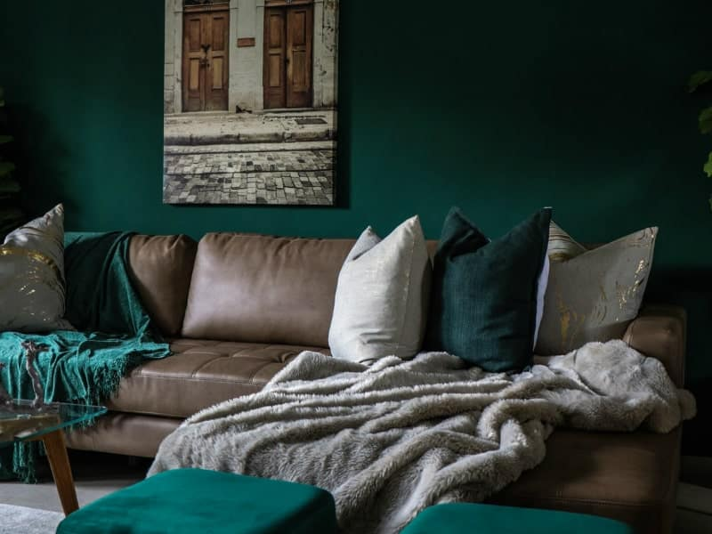 brown sofa with a blankets near the green wall